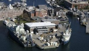 Aerial photo of the WHOI dock with research ships pulled alongside. Bigelow and Smith Labs in the background.