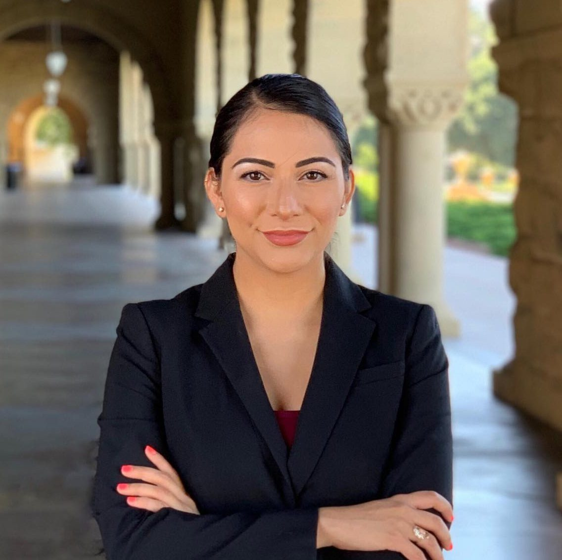 Professional head shot of Natalie Nevarez, dark haired woman in blazer, arms folded and smiling at camera.