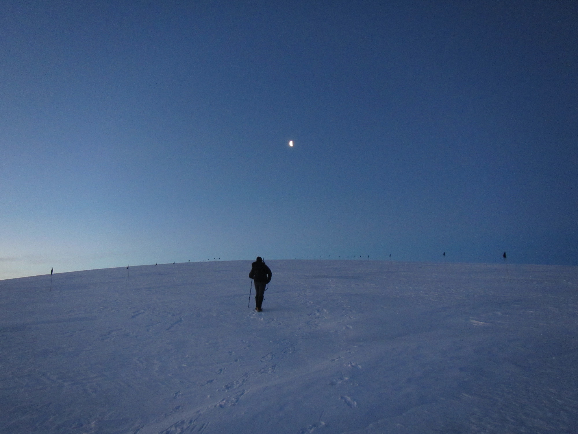 Spring days bring a twilight that last for hours. Greg makes his way up the glacier toward the rising moon.