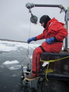 Austin Melillo, a geology student at Rutgers University, helps deploy the LTER CTD (conductivity, temperature, and depth) package amid sea ice at Station B.