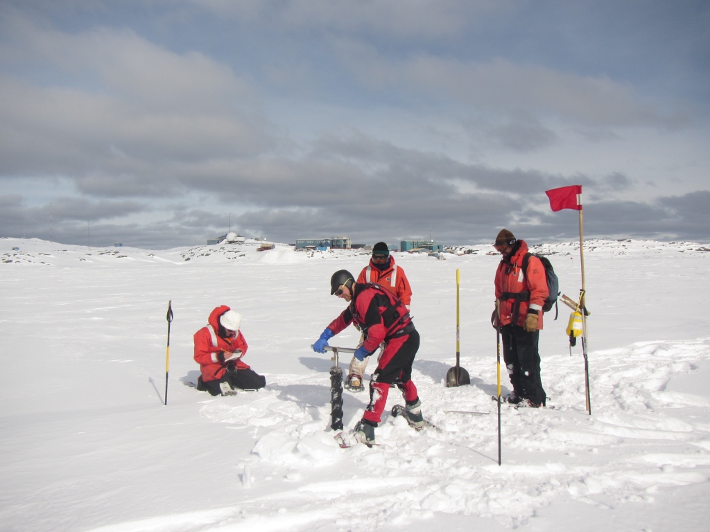 Polar microbiologist Jeff Bowman (who maintains his own blog here) uses an ice corer to establish a bore hole through the sea ice near Palmer Station, as Nicole Couto (a graduate student at Rutgers University) and members of Palmer's Glacier Search and Rescue Team, provide needed support and encouragement.