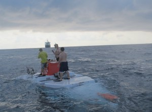 Alvin recovery swimmers Phil Santos, Peter Leonard, and Logan Driscoll meet the sub as it surfaces.