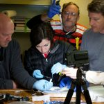 Whitman College undergraduate Gemma Wallace dissects the supergiant amphipod with a little help from (left to right) cruise Chief Scientist Tim Shank, Paul Yancey, Jeff Drazen, and Doug Bartlett. (Photo by Ken Kostel, Woods Hole Oceanographic Institution)