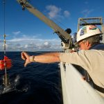 R/V Thomas G. Thompson crew member signals the crane operator to lower the revised hadal lander into the water. (Photo by Ken Kostel, Woods Hole Oceanographic Institution)