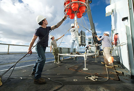 Paul Benecke, ordinary seaman on R/V Thomas G. Thompson, helps set steady a flotation pack while it is bolted in place on the hadal lander. (Photo by Ken Kostel, Woods Hole Oceanographic Institution)