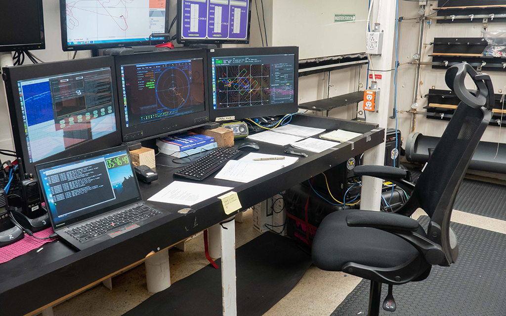 """General setting of the AUV Sentry """"watch"""" station. The rightmost screen shows NavG v.2 (Photo by Manyu Belani)"""