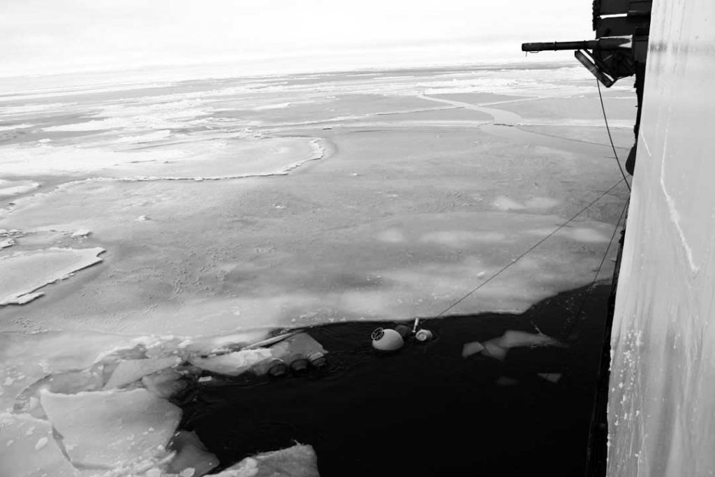 Keyhole Surgery: the moment when the bosun and crew snagged the topmost floats of the Instrument Mooring #2 at the start of the morning watch aboard ship. By lunchtime, more than 2 and one half miles of equipment had up through this small hole. Note that, the rest of the Arctic Ocean is completely frozen-over, which means we now have to break ice with the ship everywhere we go. (photo by Chris German, Woods Hole Oceanographic Institution)