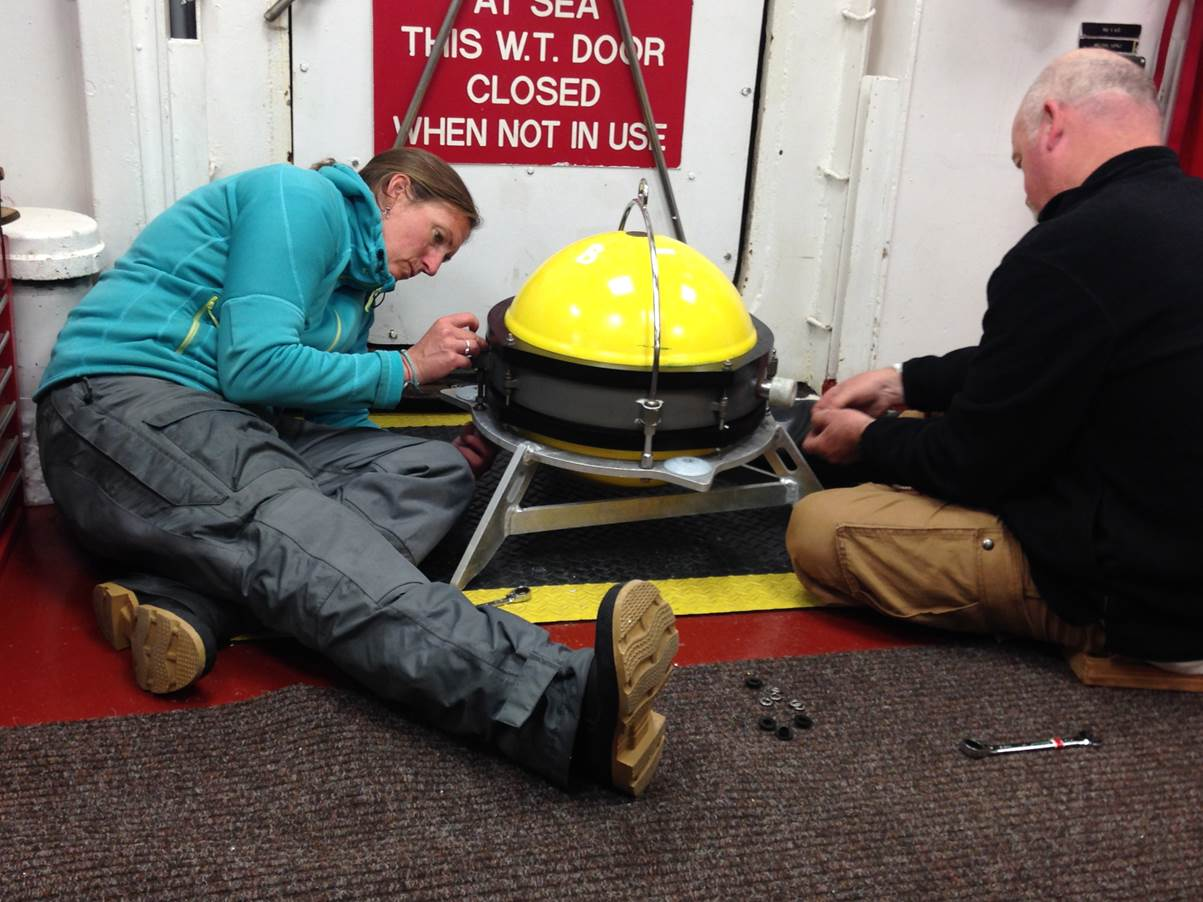 WHOI technicians Dara Tebo and Tim Kane attach a heavy tripod  to a seismometer pressure housing prior to BBOBS deployment.  The tripod helps couple the seismometer to ground motion.