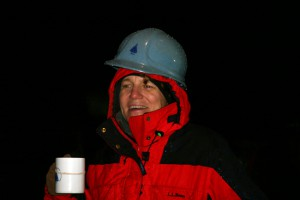 On the rainy deck of the Knorr, Amy Bower, drinking hot chocolate to keep warm, watches, as the mooring slowly unspools. (Photo by David Sutherland, Woods Hole Oceanographic Institution)