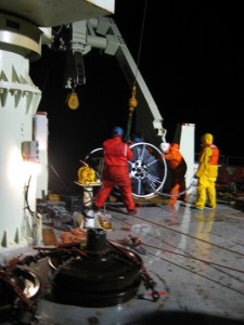 At around 1:00 a.m., EST, an hour or so after the yellow buoyancy sphere went overboard and the mooring deployment officially began, the crew wrestles the first of the two SALP frames into position. (Photo by Donovan Hohn, Woods Hole Oceanographic Institution)