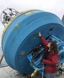 Photo of Amy standing on the back deck reaching to touch the bottom of a very large surface buoy, which is secured leaning over the back edge of the ship. When upright, the total buoy height is about five times as tall as she is.
