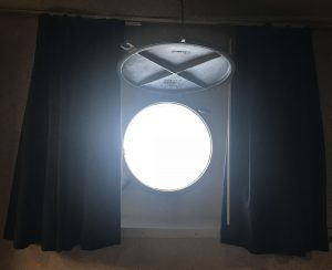 Photo of a glass-covered porthole with metal cover secured in the open position above it.