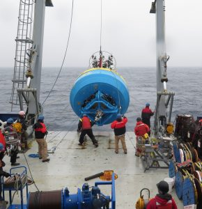 Photo of the surface buoy lifted from the deck and about to go into the water. Several deck crew are helping hold ropes to keep the buoy from swinging.