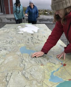 Photo of Amy touching the elevation map of southwest Iceland. Hilary and Alison are standing at the far end of the large outdoor table map
