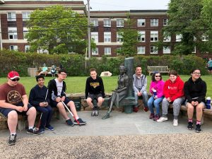 A group photo of the eight Perkins Outreach students sitting on a bench next to a statue of environmentalist Rachel Carson.