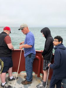 A photo of Rob Reynold,s the educator on our boat trip, and three students work to lower a dredge over the railing of our chartered boat.
