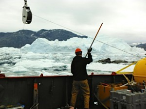 Nick Beaird fending ice off of the lines in August 2013 during a mooring recovery.