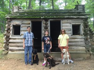 Classmates Preston and Rebecca with their new dogs, and myself and Hugger (right) in front of a commander's cabin at Jockey Hollow State Park.