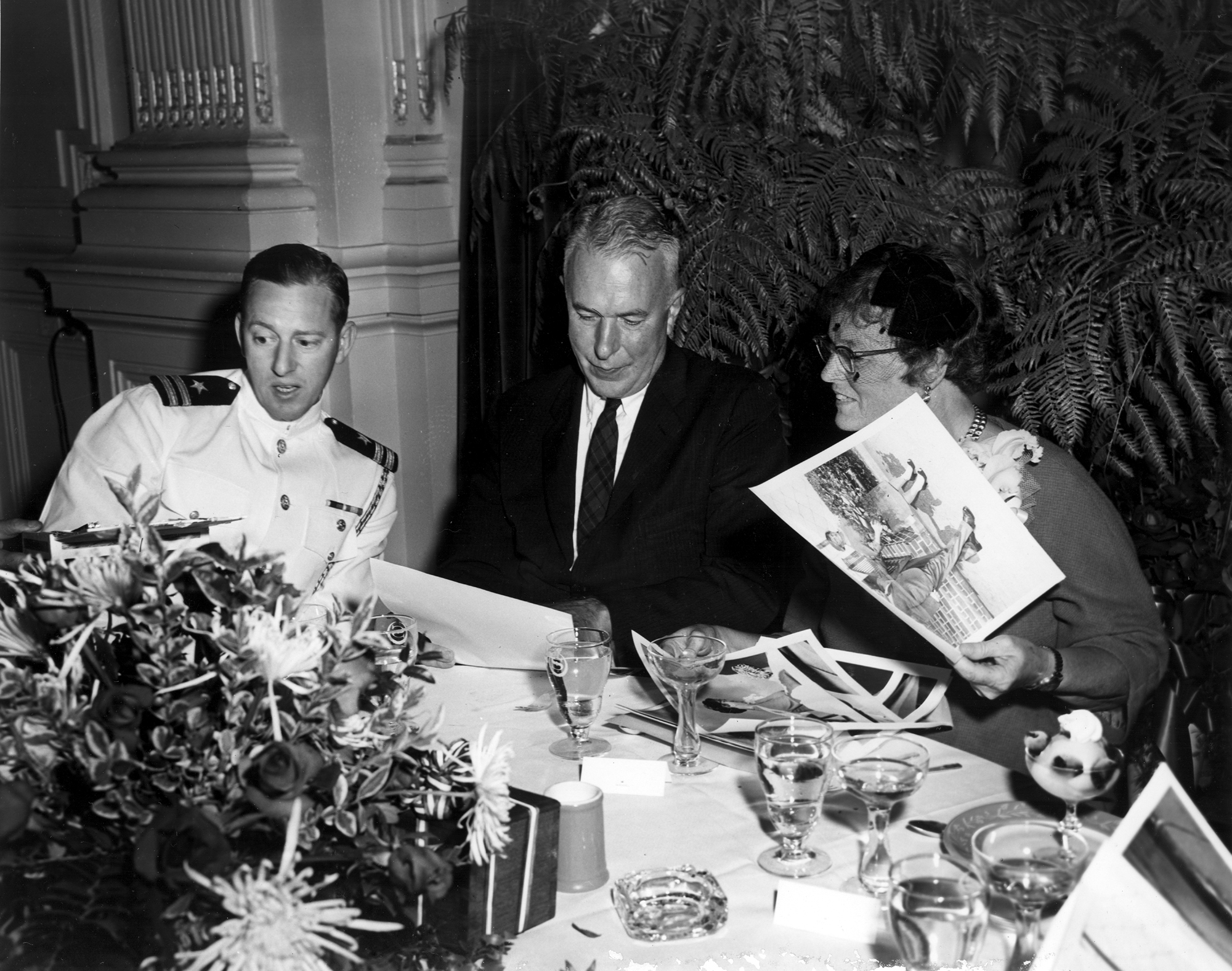 Columbus Iselin, Mary Sears and unidentified man (left) in uniform looking at photos. (Photo courtesy of WHOI Archives)